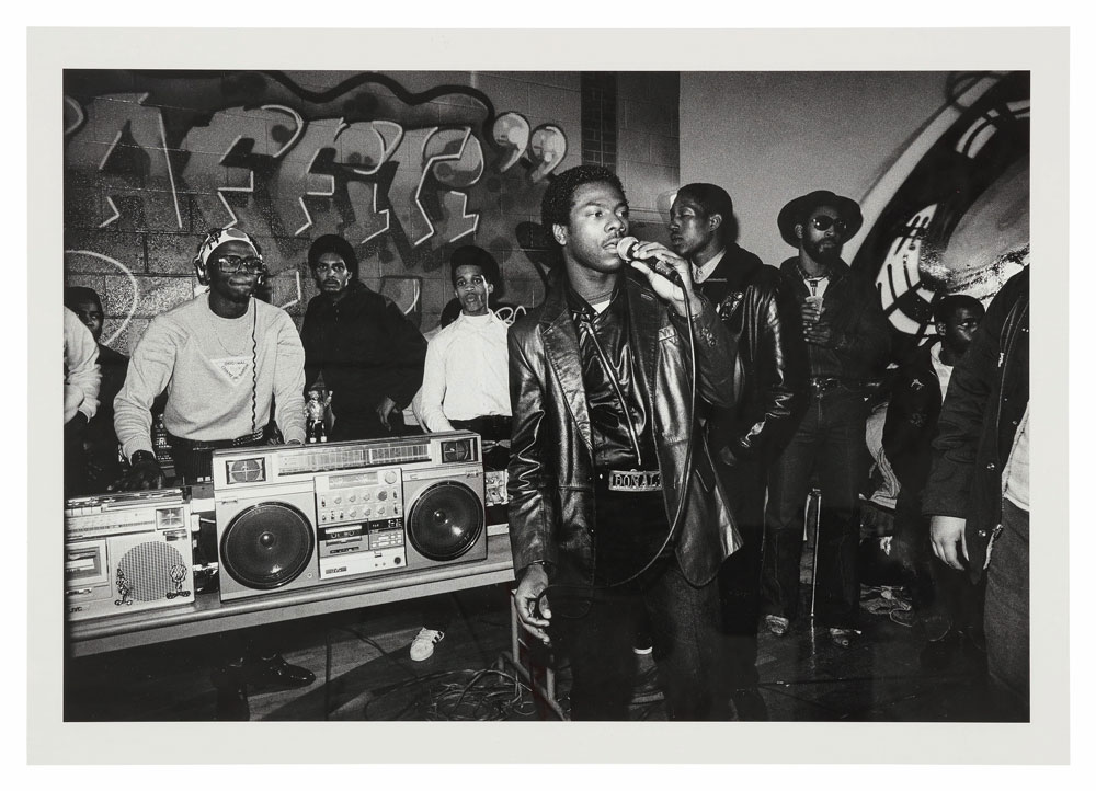 Grand Mixer D.ST on turntables, Donald D on the mic, DJ Kool Herc in hat and shades, Bronx River Center, November 12, 1983. © Sophie Bramly