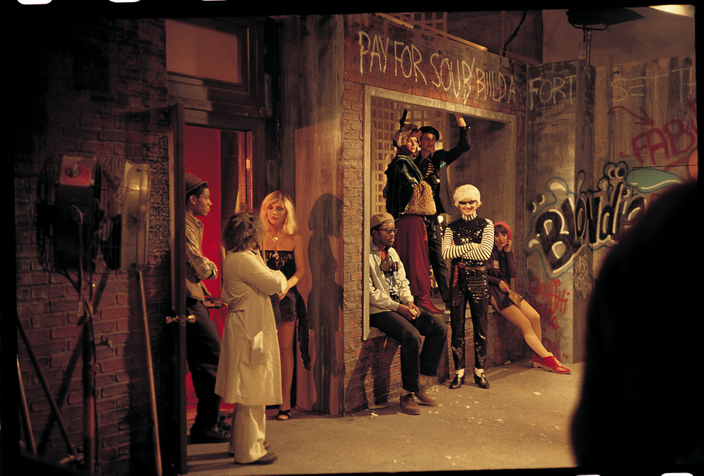 """Photography by Charlie Ahearn, [Debbie Harry, Jean-Michel Basquiat, and Fab 5 Freddy with others on the set for the music video for """"Rapture""""]"""